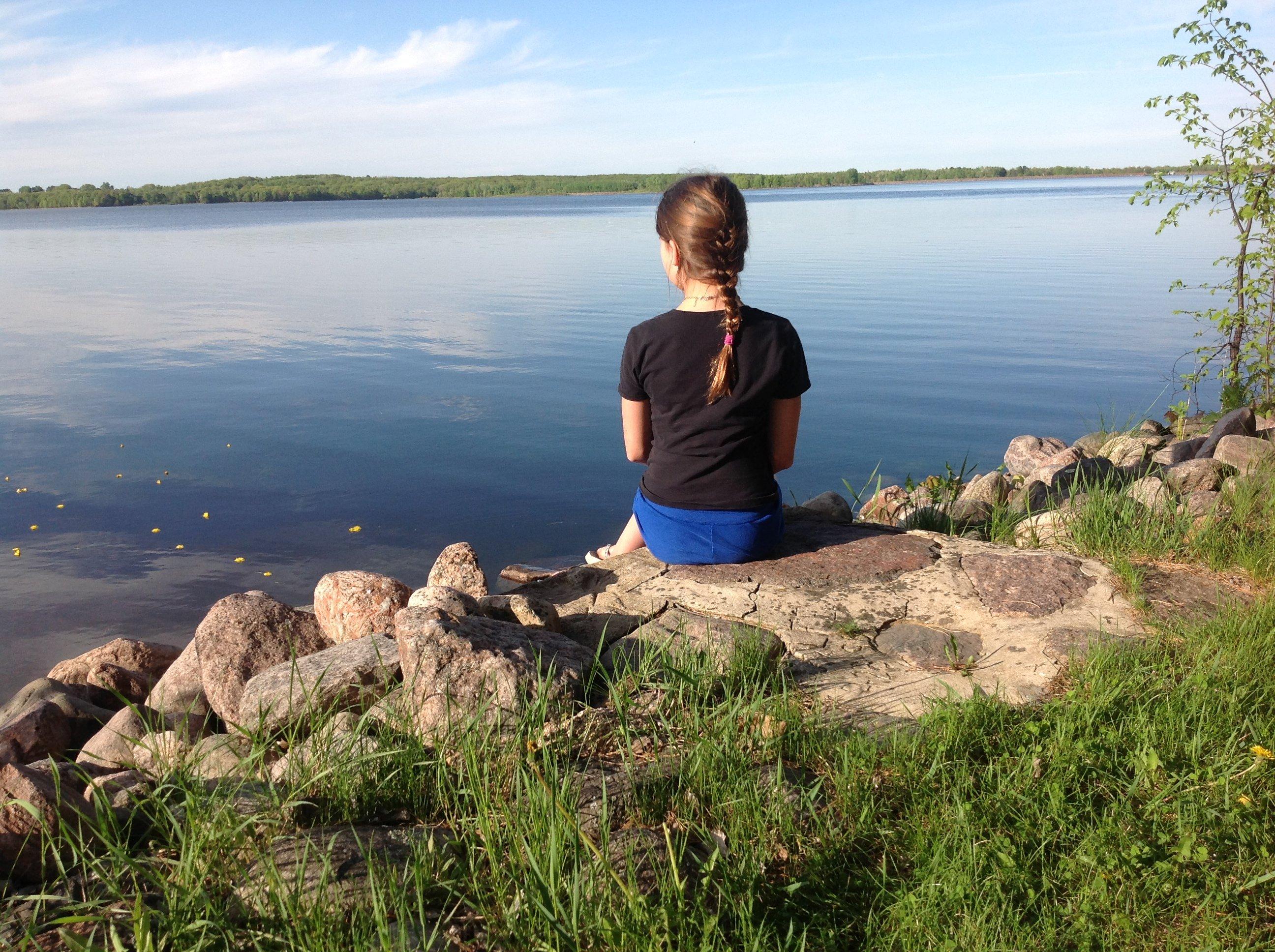 A girl staring at a lake